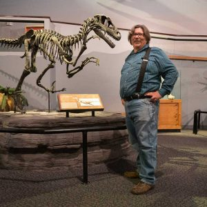 Jim Kirkland with Utahraptor skeleton